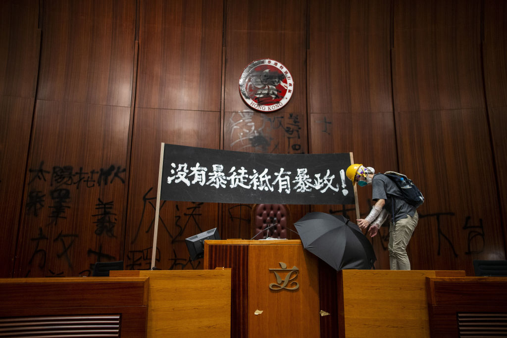 A demonstrator places an umbrella next to a banner reading 'There are no rioters, only tyranny' in Chinese, displayed inside the chamber of the Legislative Council in Hong Kong, China, on Monday, July 1, 2019.