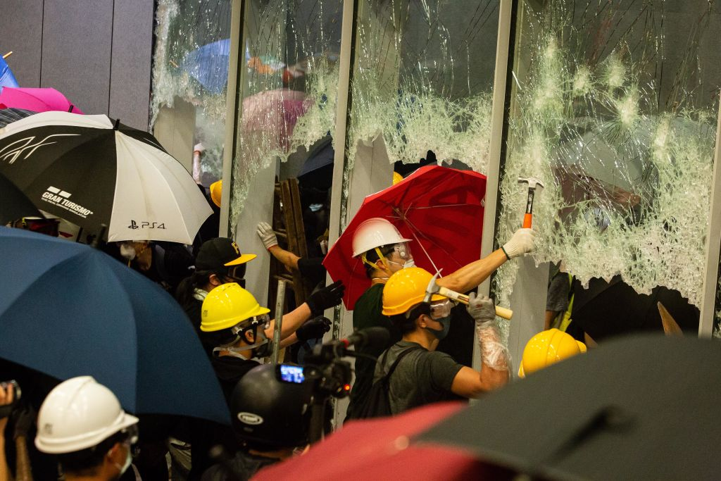 Demonstrators use hammers to break windows at the Legislative Council building during a protest in Hong Kong, China, on July 1, 2019.