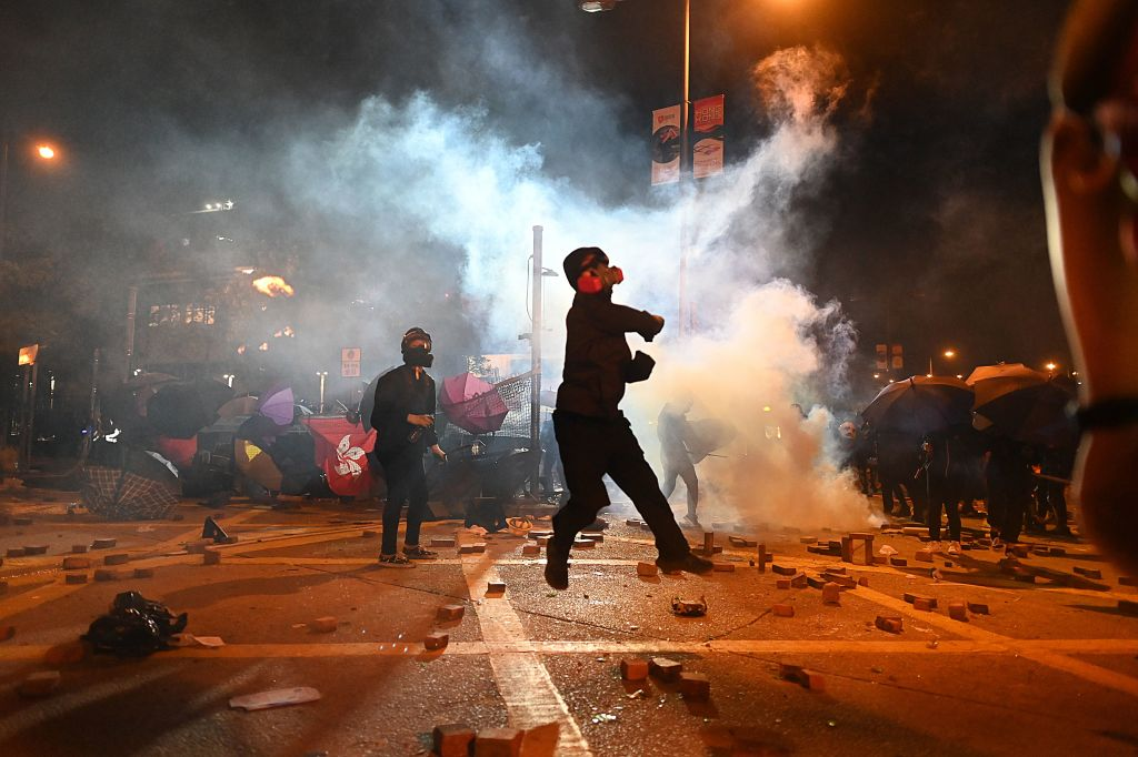 A protestor throws a petrol bomb during clashes with police outside the Polytechnic University of Hong Kong in Hung Hom district of Hong Kong on November 16, 2019.
