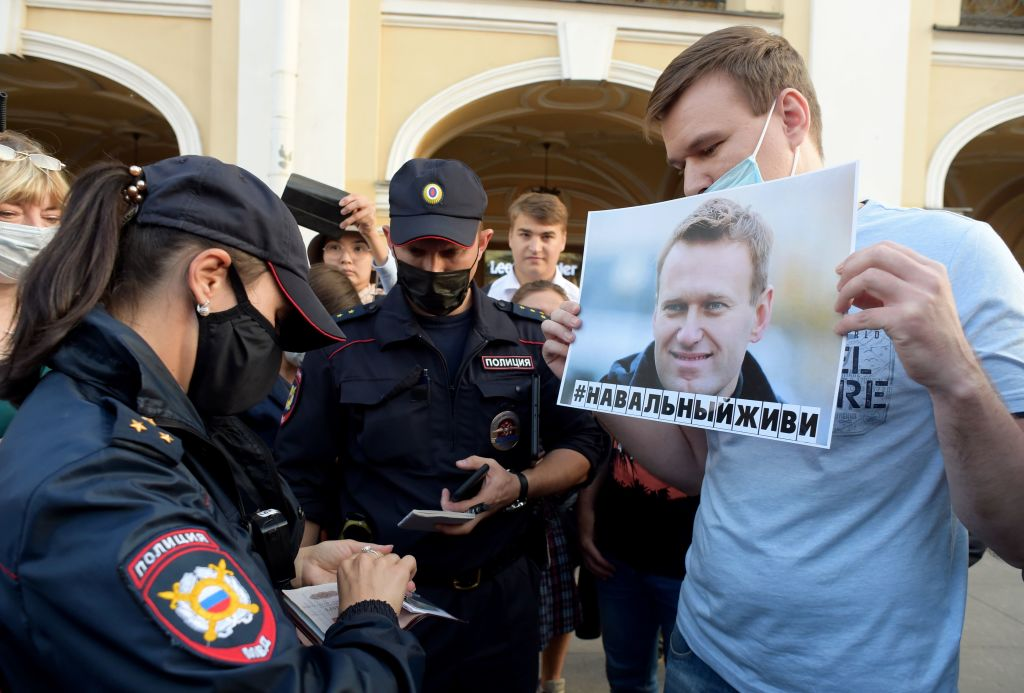 Police officers check documents of a man standing with a placard with an image of Alexei Navalny during a gathering to express support for the opposition leader after he was rushed to intensive care in Siberia suffering from a a suspected poisoning, in St. Petersburg on August 20, 2020.
