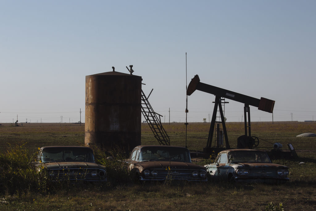 Abandoned cars sit parked in front of a pump jack near Pampa, Texas, on Sept. 26, 2020.