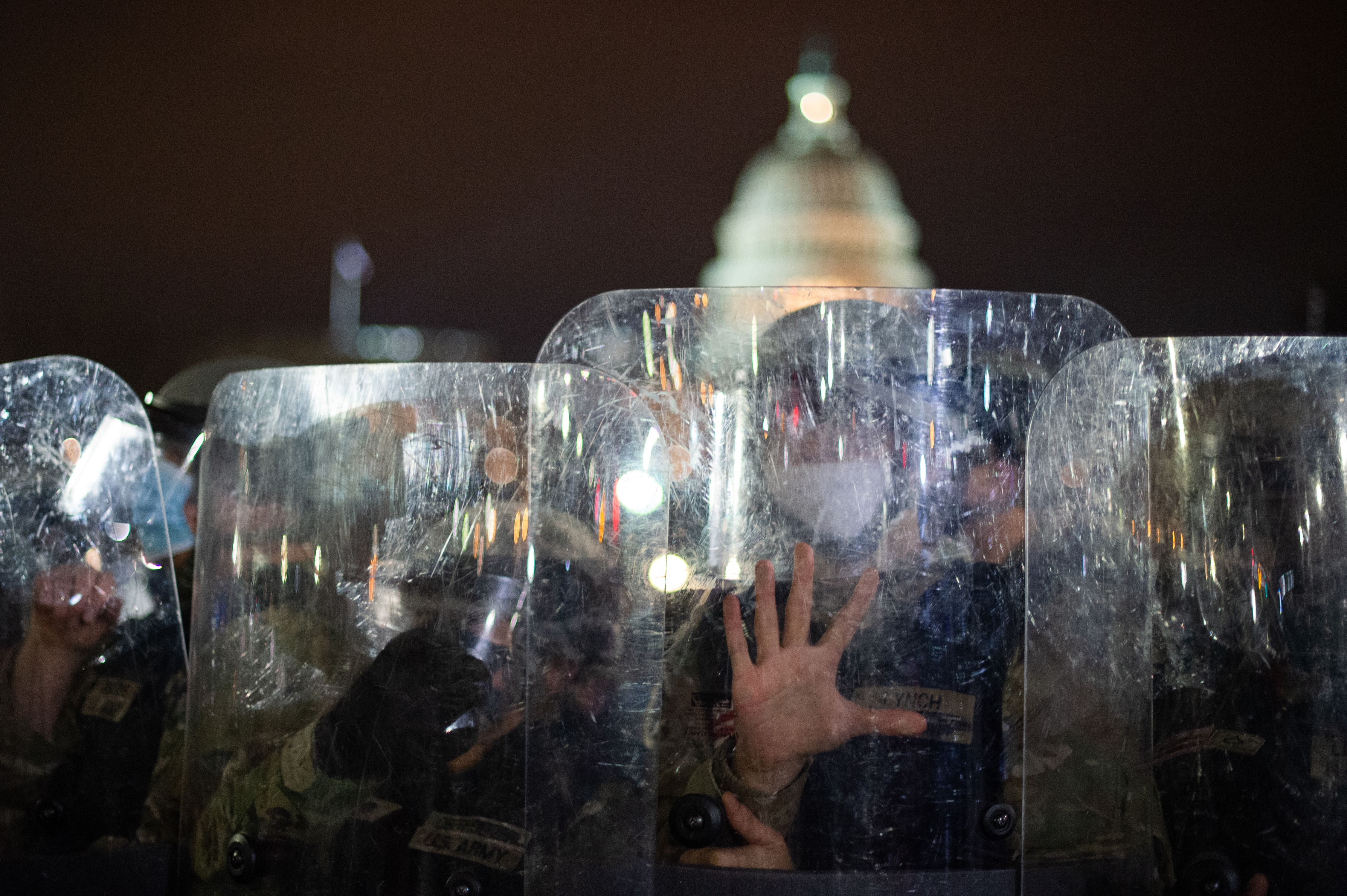 National Guard troops are seen behind shields as they clear a street from protestors outside the Capitol building on Jan. 6, 2021 in Washington, D.C.