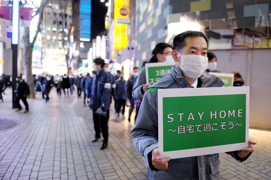 Members of the Tokyo Metropolitan Government holding placards on the street ask people to stay at home due to the spread of the coronavirus on January 8th, 2021, in Tokyo, Japan.
