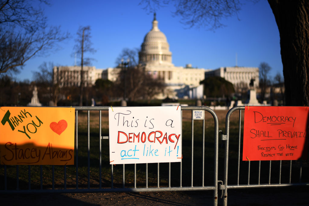 People place pro-democracy signs at a fence near the US Capitol building three days after it was stormed, invaded and vandalized by Trump rioters in Washington, Jan. 9, 2021.