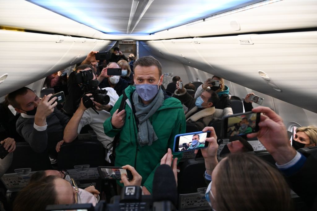 Russian opposition leader Alexei Navalny walks to take his seat in a Pobeda airlines plane heading to Moscow before take-off from Berlin Brandenburg Airport (BER) in Schoenefeld, southeast of Berlin, on Jan. 17, 2021