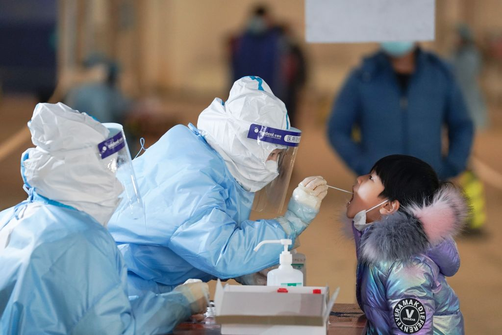 A medical worker collects a swab sample from a child at a COVID-19 testing site in Daxing District of Beijing, capital of China, Jan. 20, 2021.