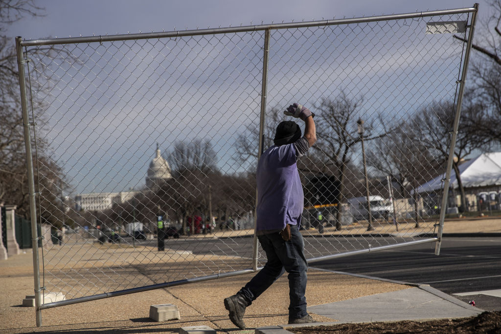 A worker removes fencing a day after the inauguration of President Joe Biden in Washington, D.C., on Jan. 21.