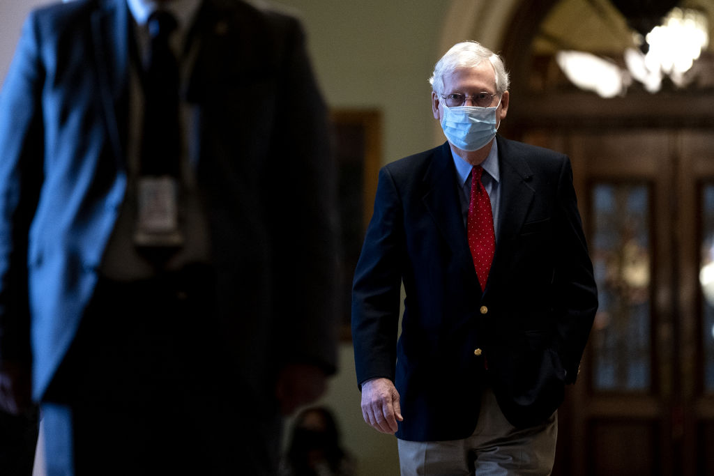 Senate Minority Leader Mitch McConnell, a Republican from Kentucky, right, wears a protective mask while walking to his office from the Senate Chamber at the U.S. Capitol in Washington, D.C., on January 22, 2021.