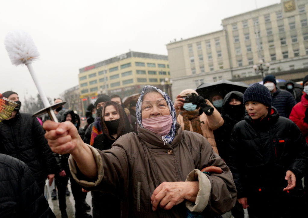 A woman holds a toilet brush as she takes part in an unauthorized rally in support of Russian opposition activist Alexey Navalny.