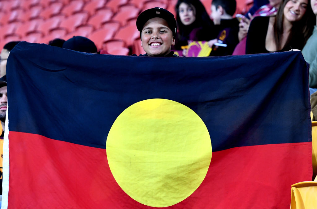 A young Indigenous fan shows his support during the round 12 NRL match between the Brisbane Broncos and the Cronulla Sharks on July 31, 2020 in Brisbane, Australia.