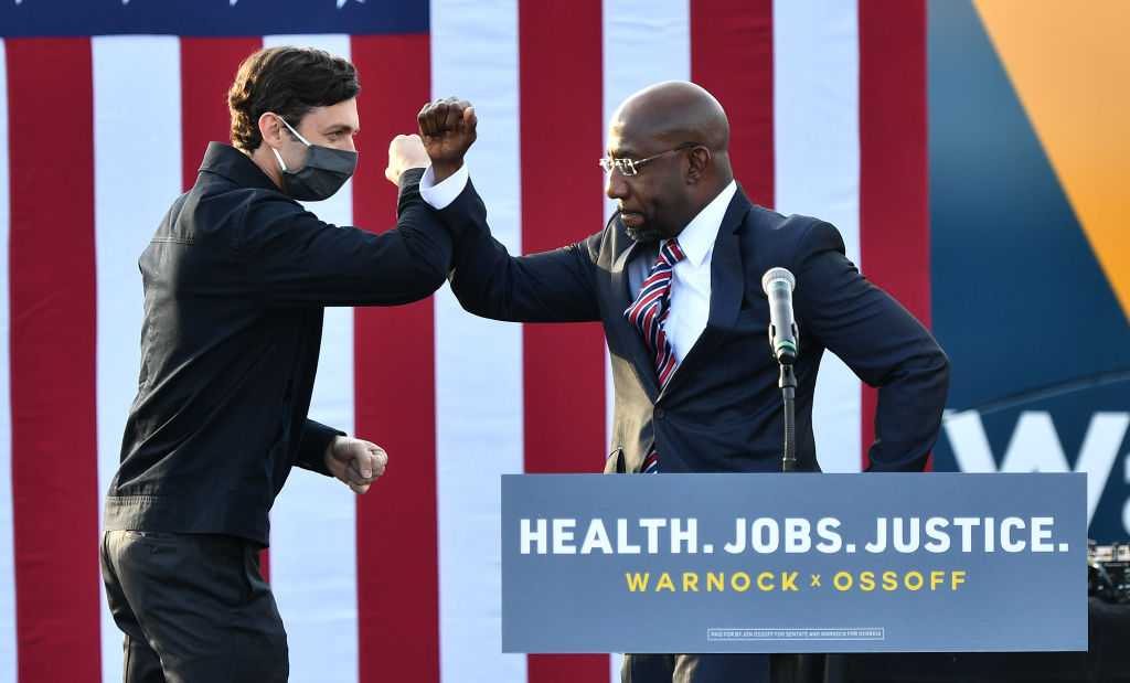Georgia Democratic Senate candidates Jon Ossoff and Raphael Warnock greet each other onstage during the  Vote GA Blue  concert for Georgia Democratic Senate candidates Raphael Warnock and Jon Ossoff at New Birth Church in Stonecrest, Georgia, on December 28, 2020.