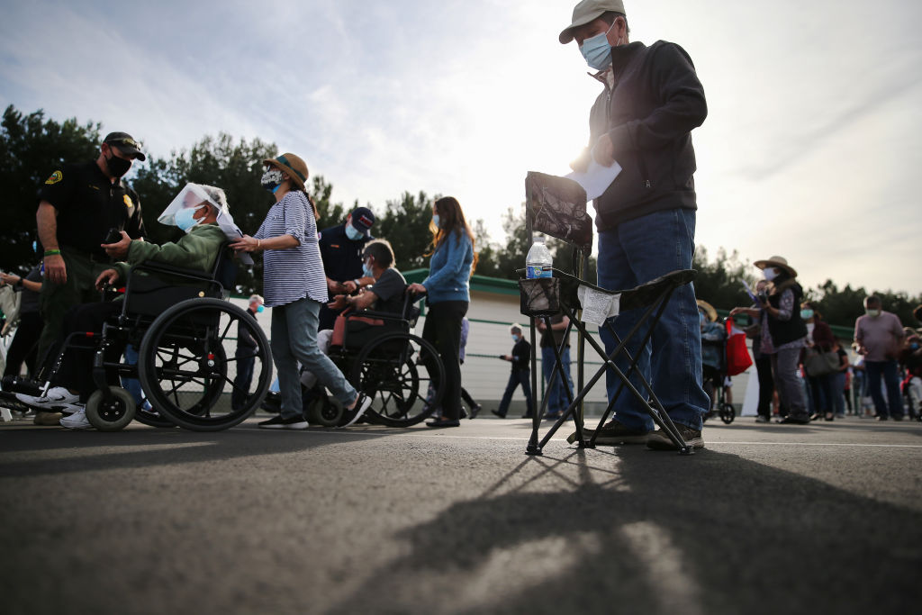 People wait in line to receive the COVID-19 vaccine at a mass vaccination site in a parking lot for Disneyland Resort on January 13, 2021 in Anaheim, California.