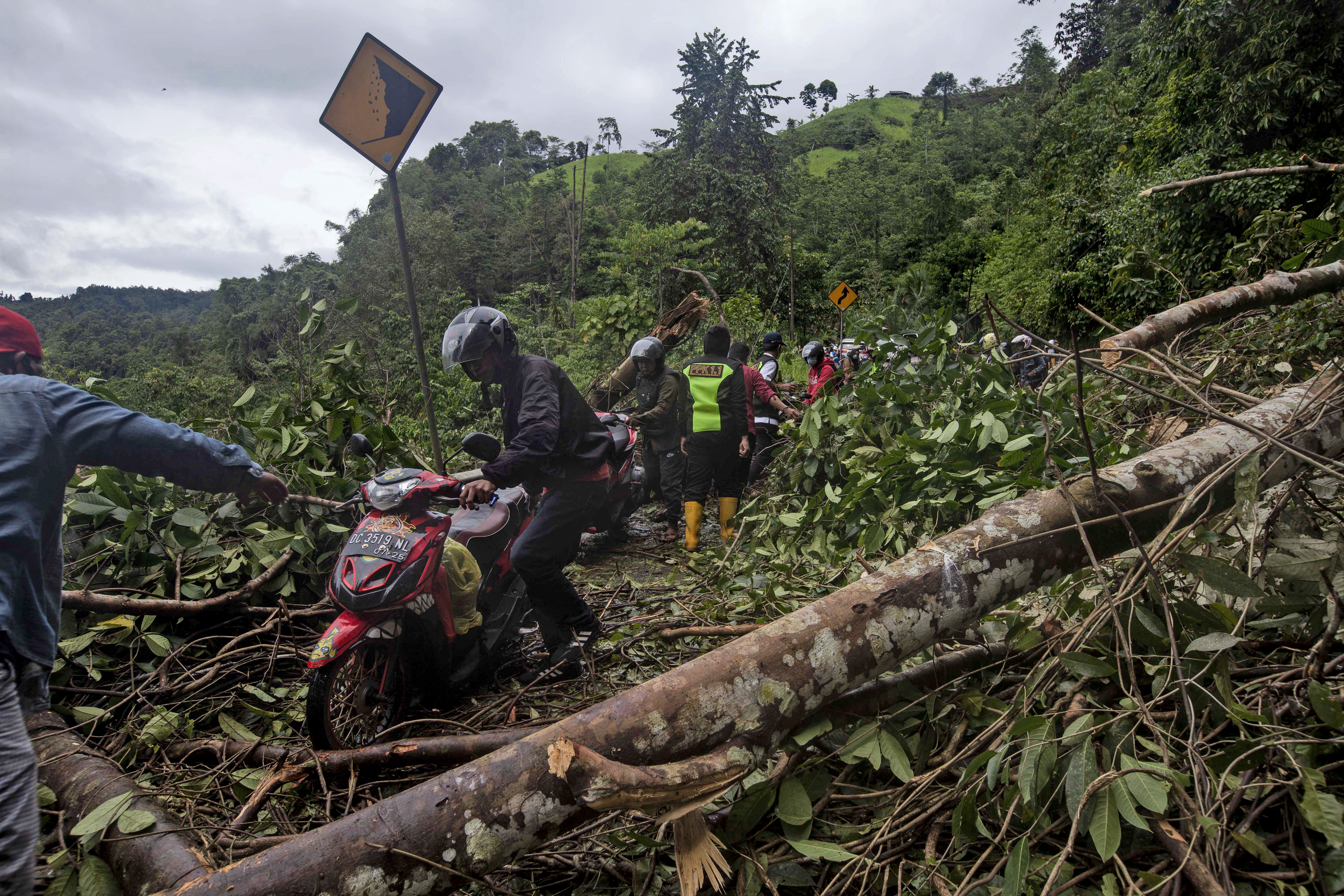 Motorists make their way through a road affected by an earthquake-triggered landslide near Mamuju, West Sulawesi, Indonesia, on Jan. 16, 2021.