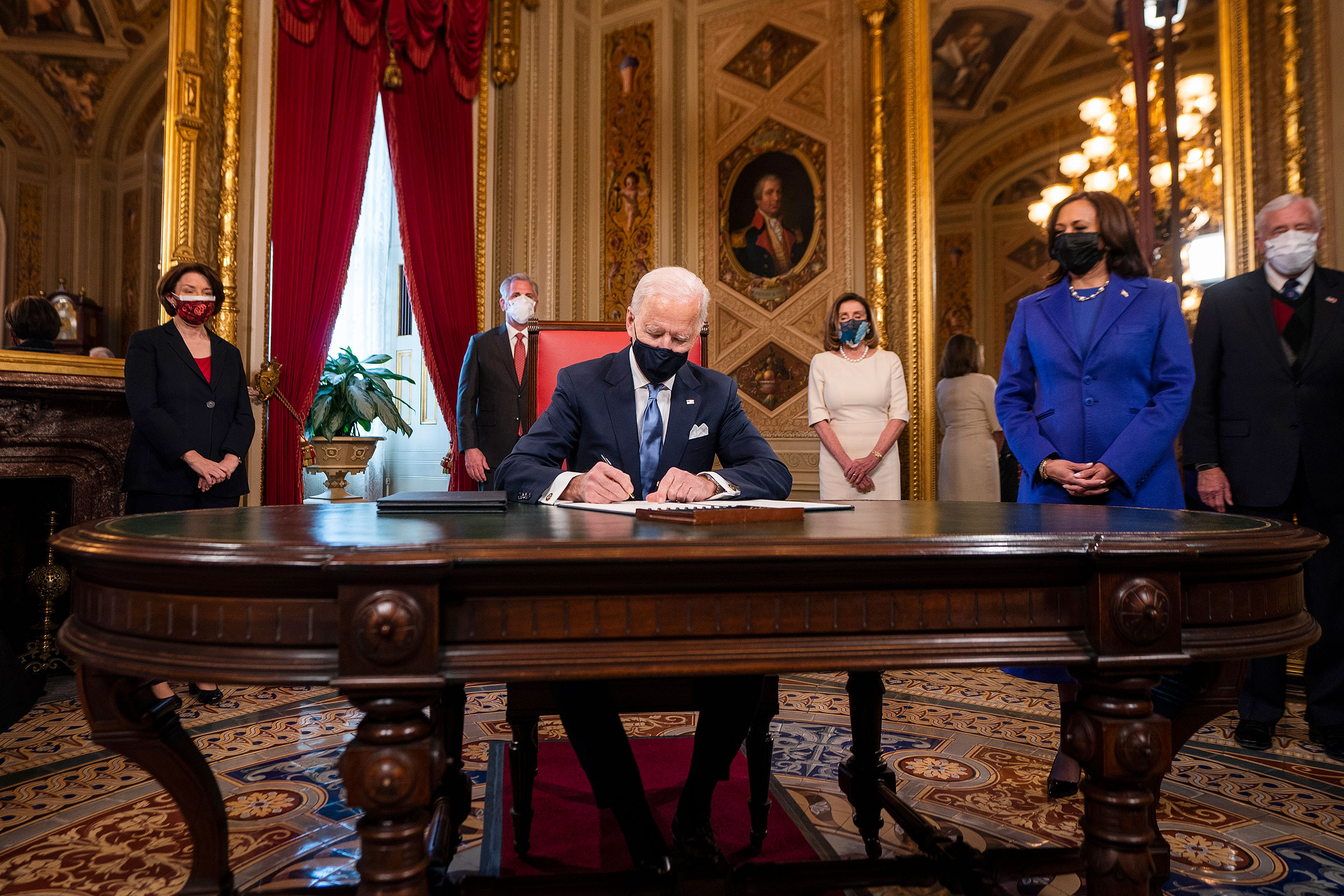 Biden signs his first official documents as President at the U.S. Capitol