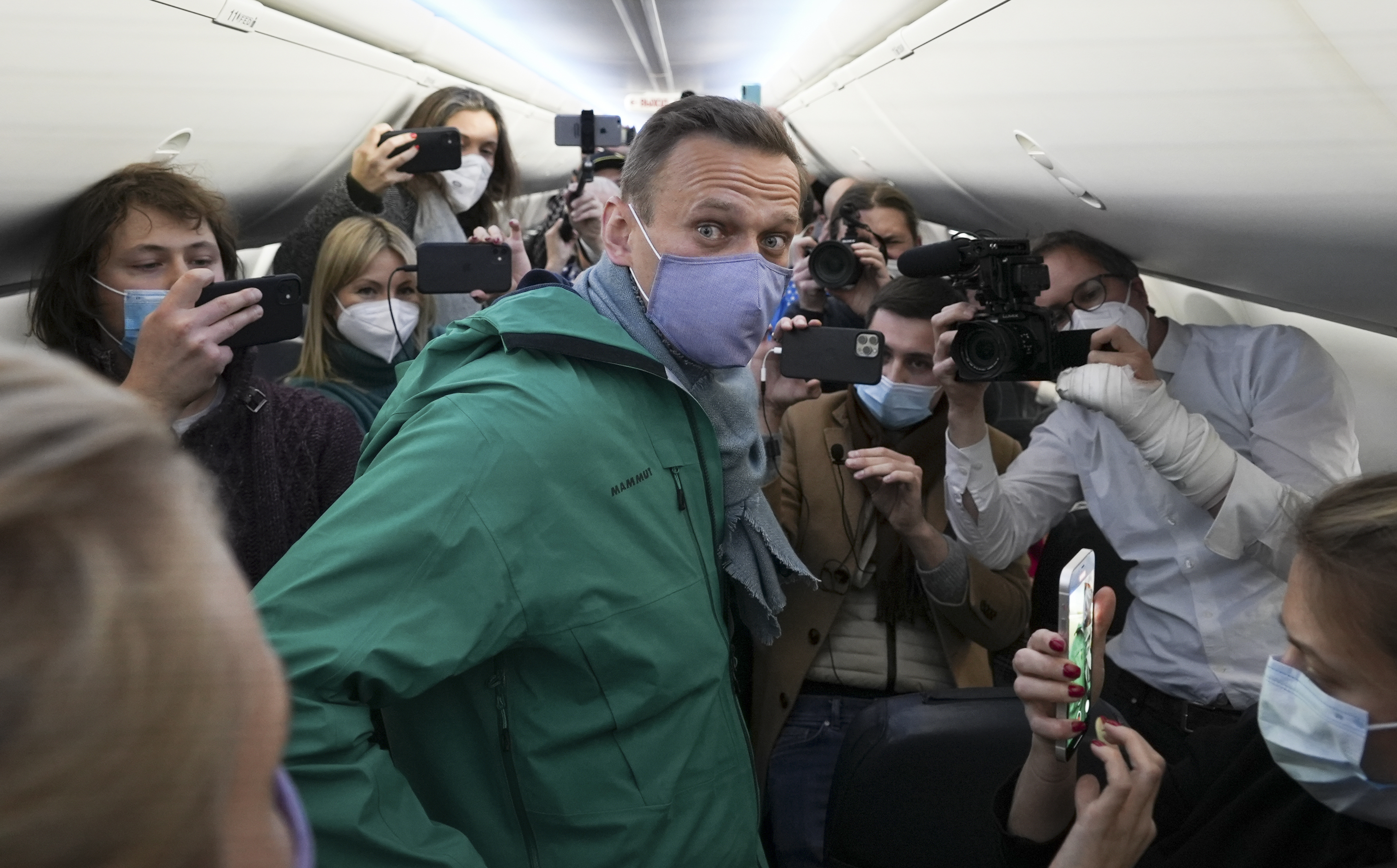 Alexei Navalny is surrounded by journalists inside the plane prior to his flight to Moscow in the Airport Berlin Brandenburg (BER) in Schoenefeld, near Berlin, Germany, on Jan. 17, 2021.