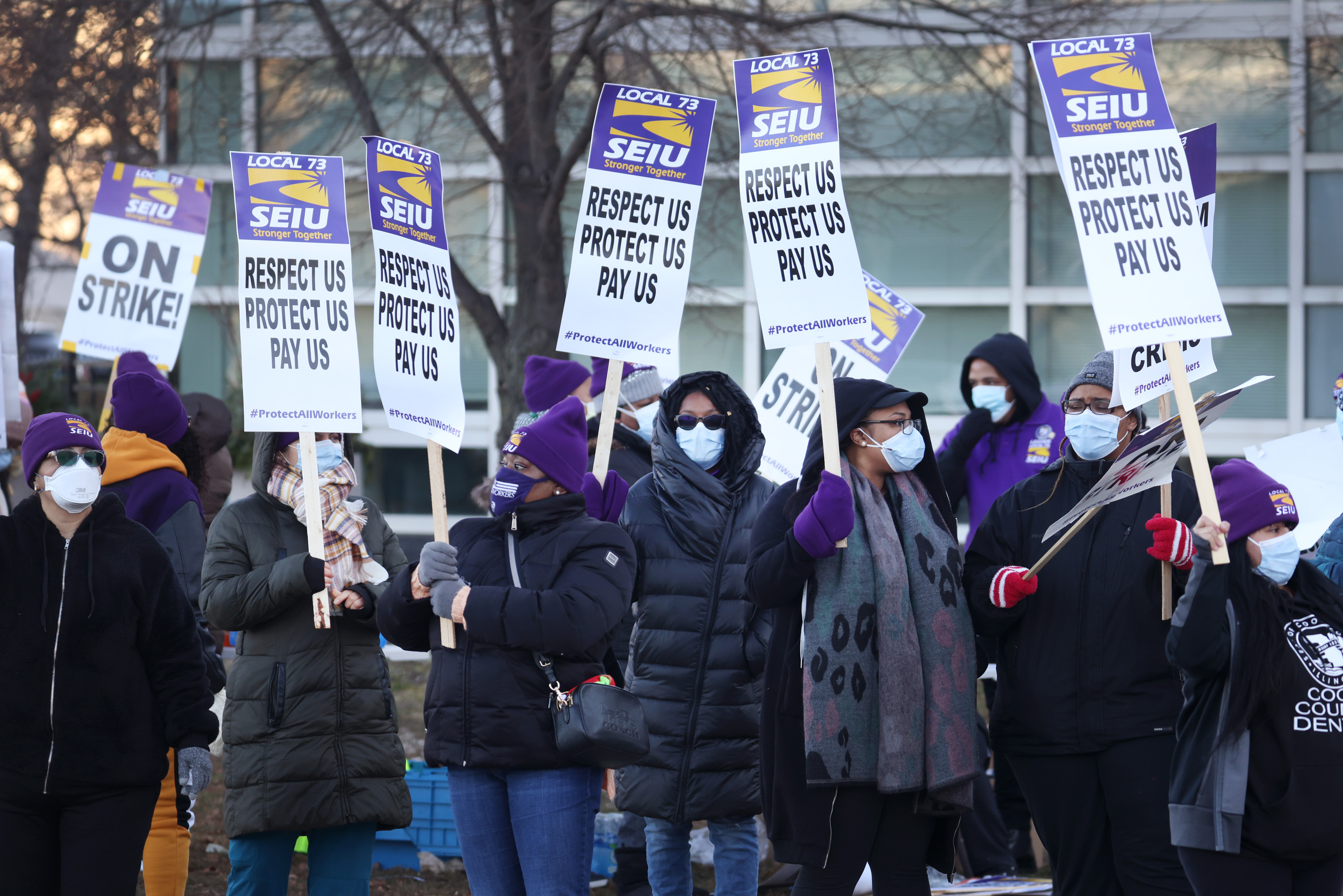 Healthcare workers with Cook County Health picket outside of Stroger Hospital as they stage a one-day strike on December 22, 2020 in Chicago. Among other issues, the workers were demanding an additional $5-per-hour for those who work with COVID-19 patients, adequate PPE supplies for all workers, and the opportunity to work from home when possible.