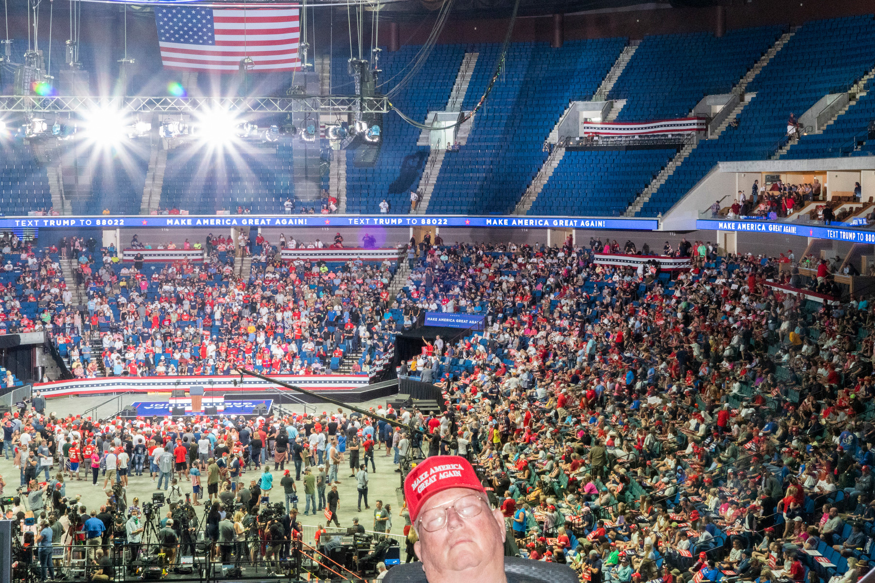 Tulsa, June 20, 2020.  I feel like this country is increasingly living in parallel worlds. The Trump rally today was bizarre. Indoors, everyone bunched together, barely anybody wearing a mask. I looked like an alien in my respirator and goggles. I was mocked a bit, and responded with my story of seeing trucks filled with bodies in New York at the height of the pandemic's first wave in America. I suppose this will be a super-spreader event. George Floyd was not mentioned even once. As people started to stream out during the 90-minute speech, I left to see if there would be confrontations with protesters. There were some scattered shouting matches and a bit of scuffling, but mostly the two groups left one another alone. One attendee of the rally carried a handmade cross, and a protester tried to snatch it out of his hand. He yanked it back, held it in the air and started chanting, 'Peace, peace, peace.' The crowd of protesters and Trump supporters around him took up the chant, filling the air. That night, my colleague Ruddy Roye and I sat down with some Trump supporters at our hotel and had drinks. It was a surprisingly thoughtful and nuanced conversation.