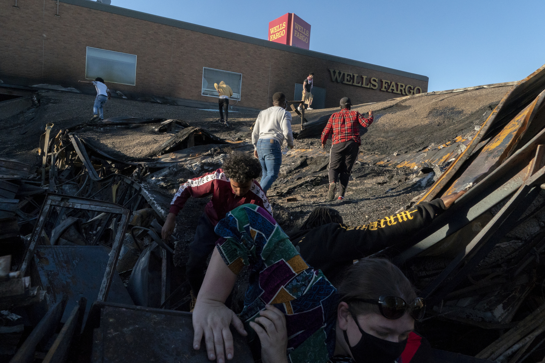 Minneapolis, May 30, 2020. People visit and take selfies on the collapsed roof of a Wells Fargo, destroyed in the riots and arson that followed the killing of George Floyd.