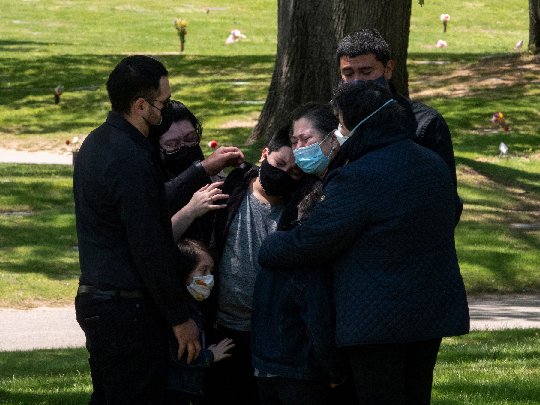 Queens, N.Y., May 13, 2020. The family of Salvador Calderon mourns his death from COVID-19 at Maple Grove Cemetery.