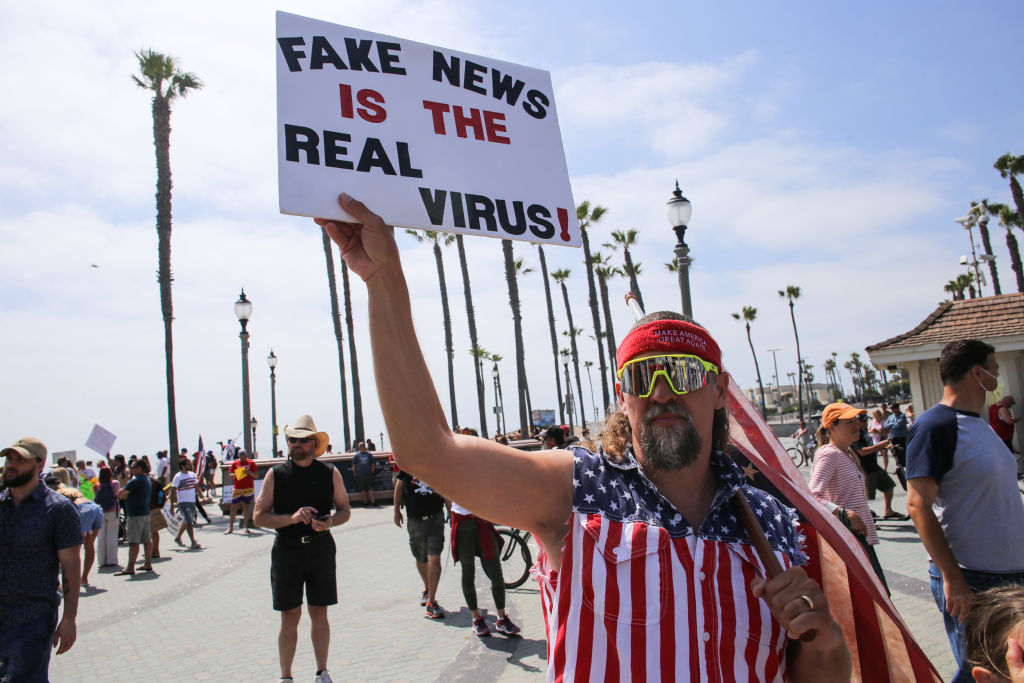 A protester holds a placard that says Fake News Is The Real Virus during a demonstration on May 9, 2020, in California.