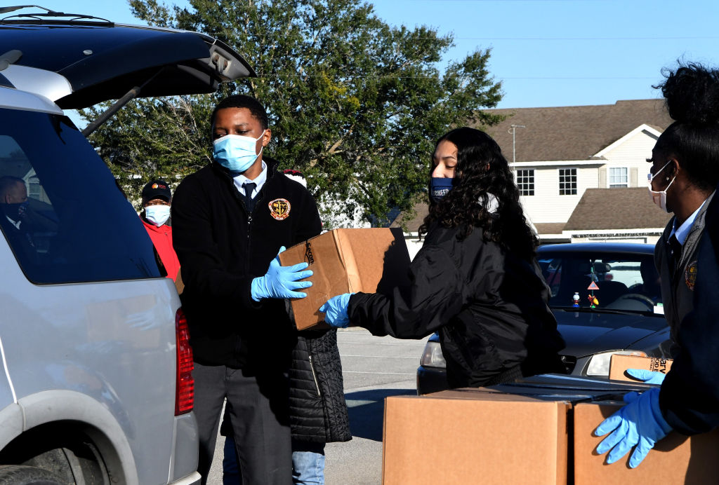 Volunteers load boxes of food assistance into cars at the Share Your Christmas food distribution event sponsored by the Second Harvest Food Bank of Central Florida, Faith Neighborhood Center, and WESH 2 at Hope International Church on December 9, 2020 in Groveland, Florida, near Orlando. Central Florida food banks struggle to serve those facing food insecurity during the holiday season amid the COVID-19 pandemic.