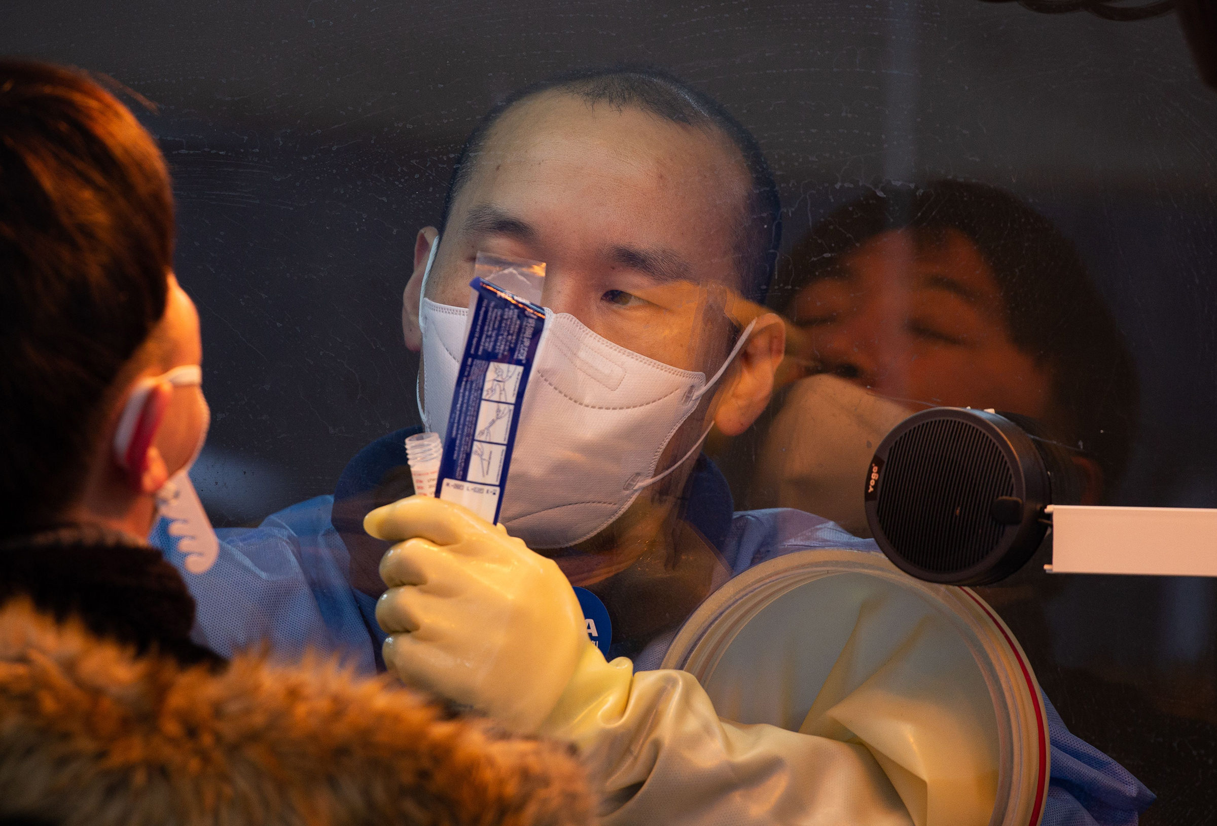 A health worker collects swabs from a citizen for COVID-19 testing at a makeshift clinic outside the Seoul city hall on Jan. 5