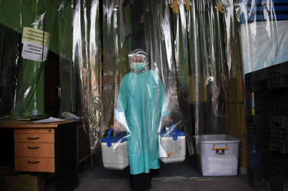 A health worker delivers containers of Covid-19 vaccines produced by China's Sinovac from a cold room in Bandung on Jan. 13 as the sprawling archipelago of nearly 270 million kicks off a mass innoculation drive in a bid to control soaring case rates