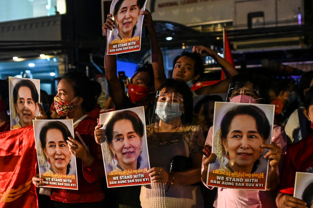 Supporters of the National League for Democracy (NLD) party hold posters with the image of Myanmar state counsellor Aung San Suu Kyi as supporters celebrate in front of the party's headquarters in Yangon on November 9, 2020, as NLD officials said they were confident of a landslide victory in the weekend's election.
