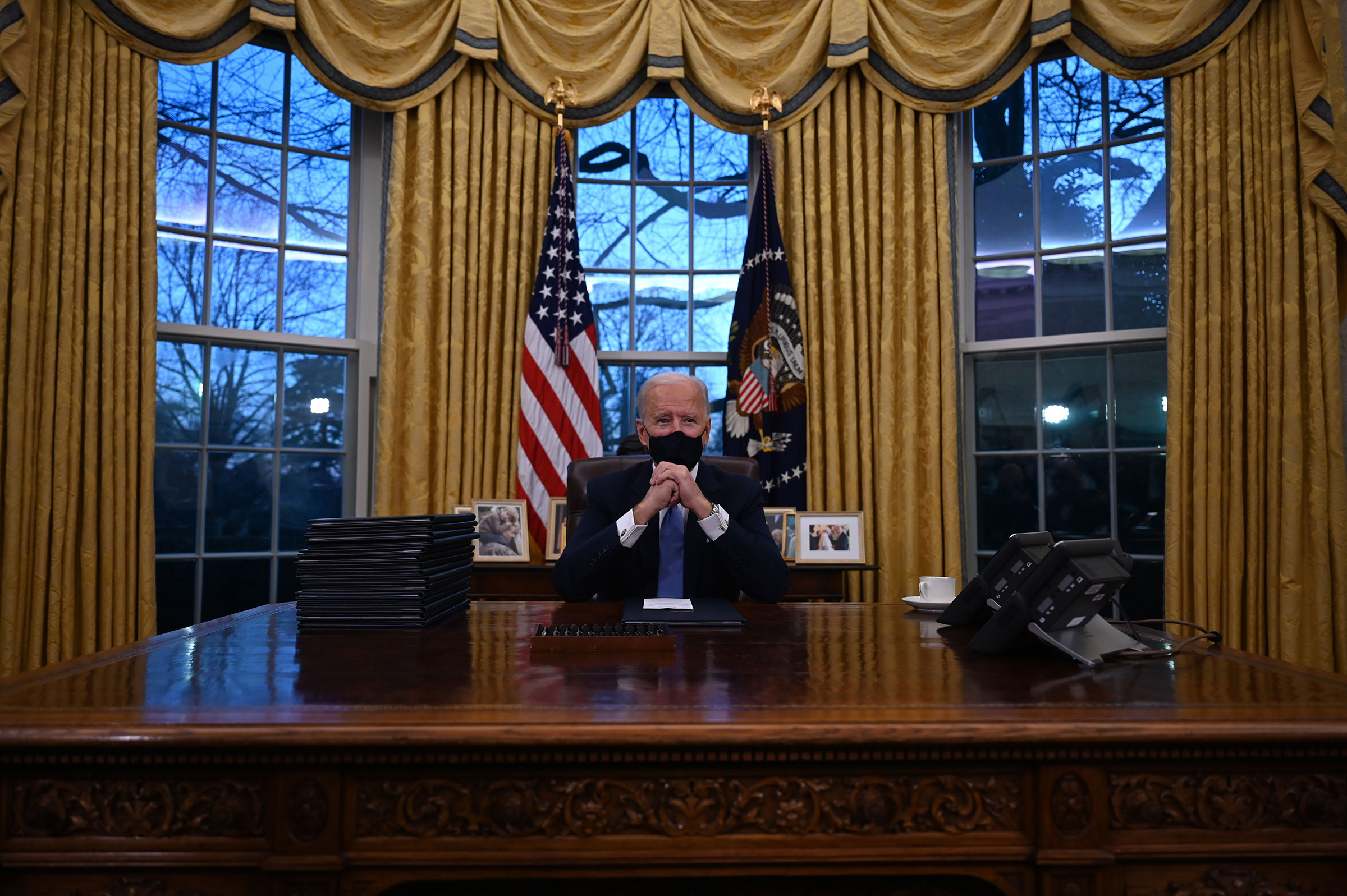 President Joe Biden sits in the Oval Office at the White House, after being sworn in.