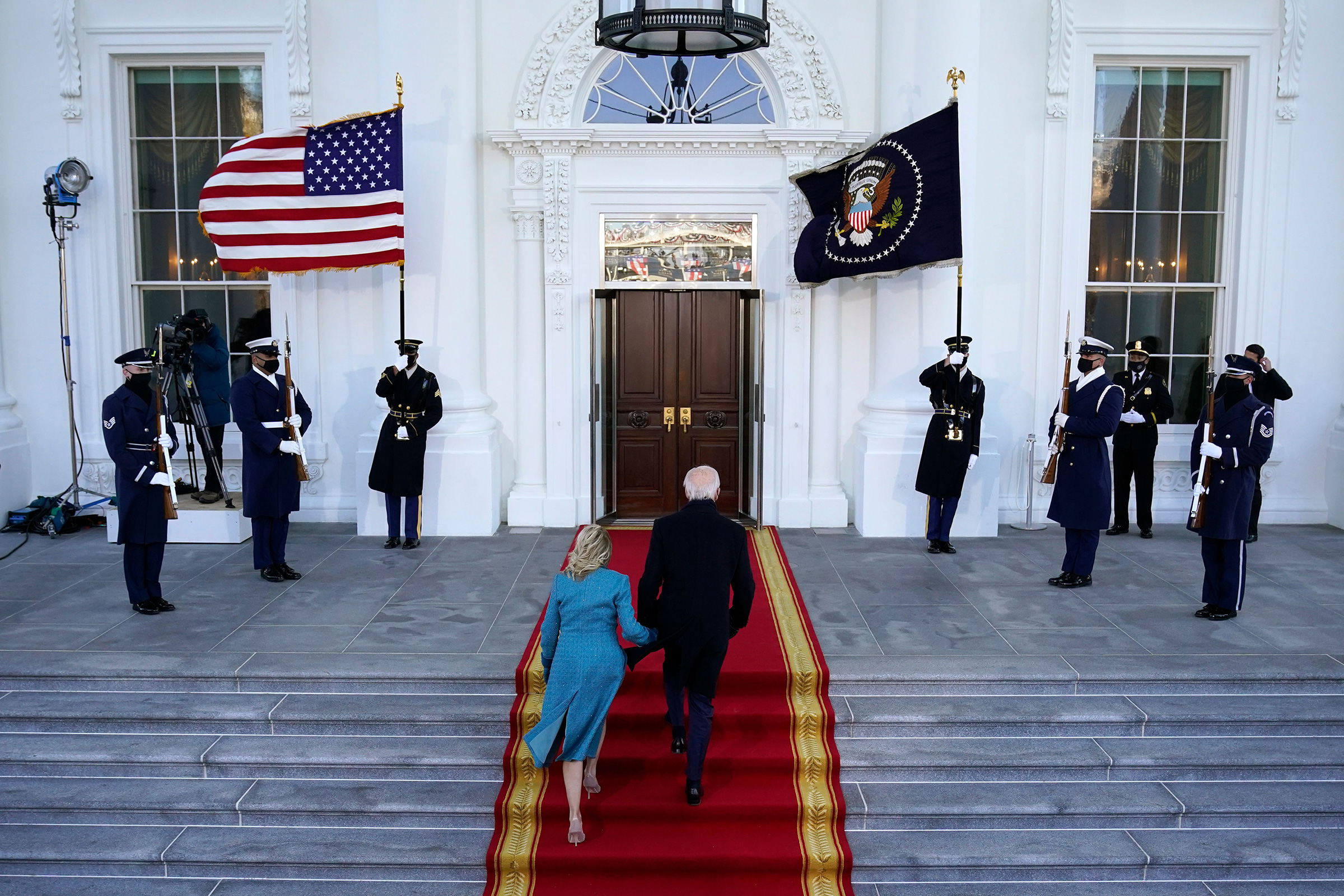 President Joe Biden and first lady Dr. Jill Biden walk up the stairs as they arrive at the North Portico of the White House.