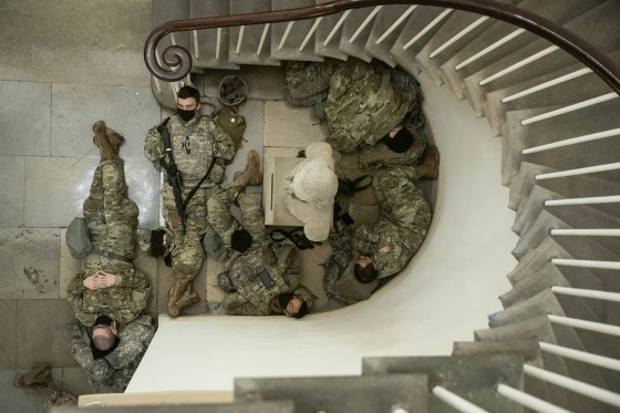 Members of the National Guard rest in a hallway of the Capitol building in Washington, on Jan. 13, 2021.