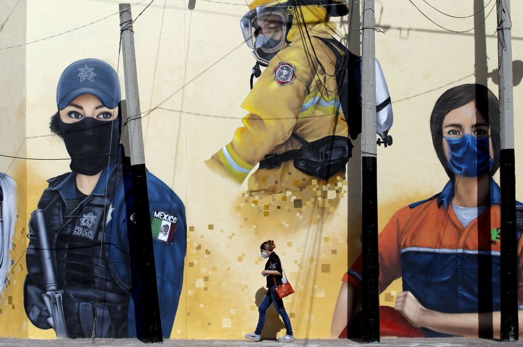 A woman walks in front of a mural, painted by workers of the Zapopan city hall as part of the program  Zapopart , as a tribute to essential workers who have cared for citizens during the COVID-19 pandemic in Zapopan, state of Jalisco, Mexico, on Aug. 12