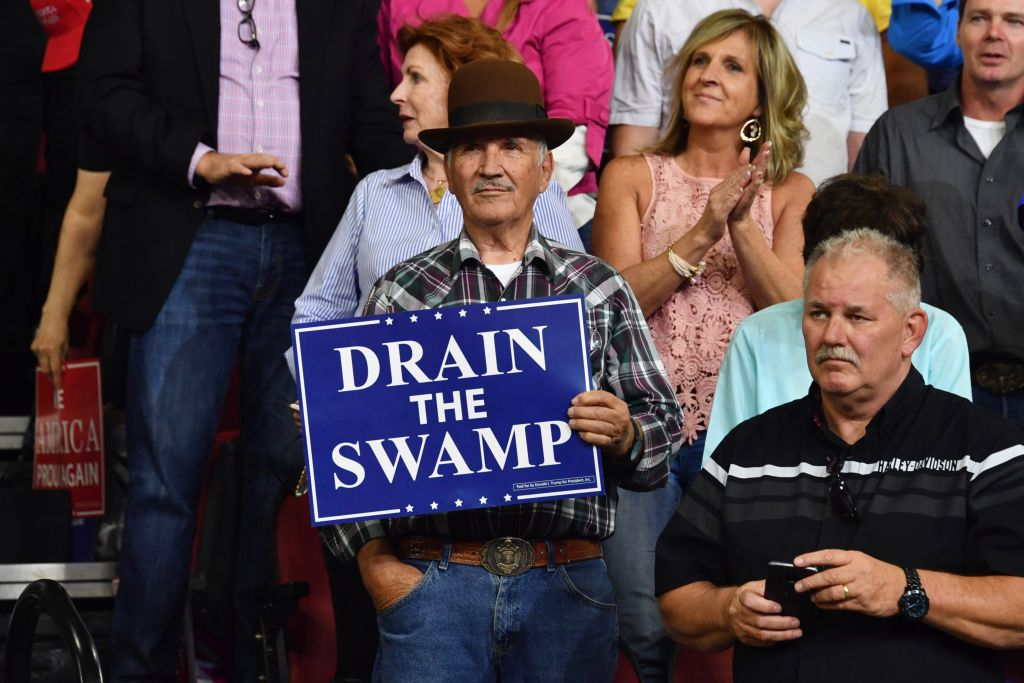 A supporter of President Donald Trump holds up a sign reading  drain the swamp  during a  Make America Great Again  rally in Billings, Montana on Sept. 6, 2018.