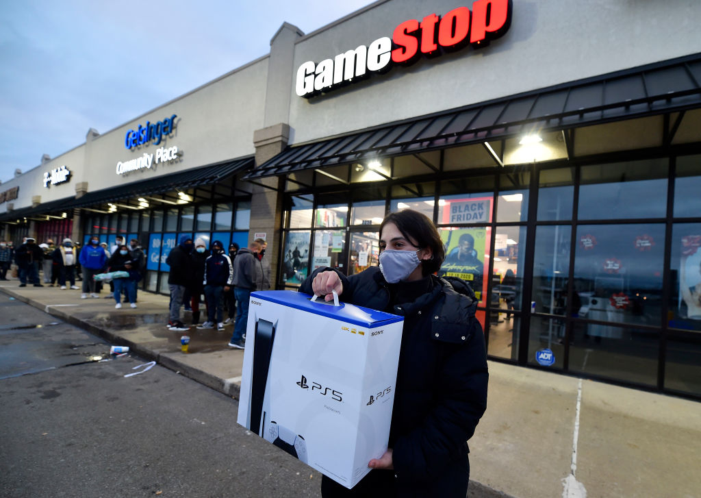 A man wearing a face masks leaves GameStop with the new PlayStation 5 gaming console on Black Friday, 2020.