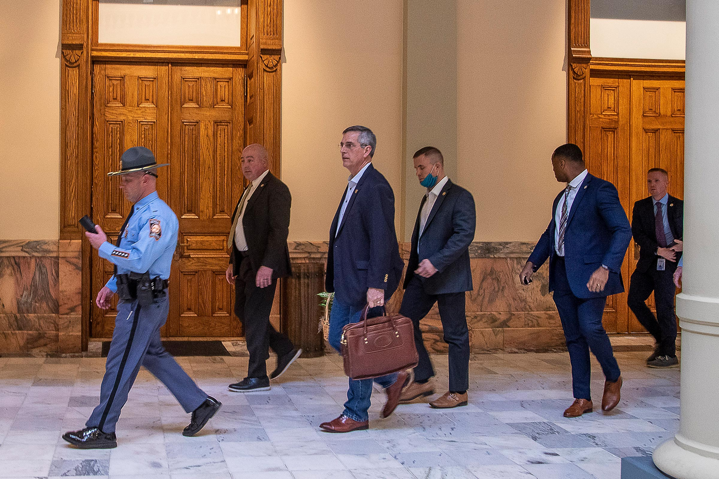 Lead by a Georgia State Trooper, Georgia Secretary of State Brad Raffensperger, center, exits the Georgia State Capitol building after hearing reports of threats, in Atlanta, Jan. 6, 2021.