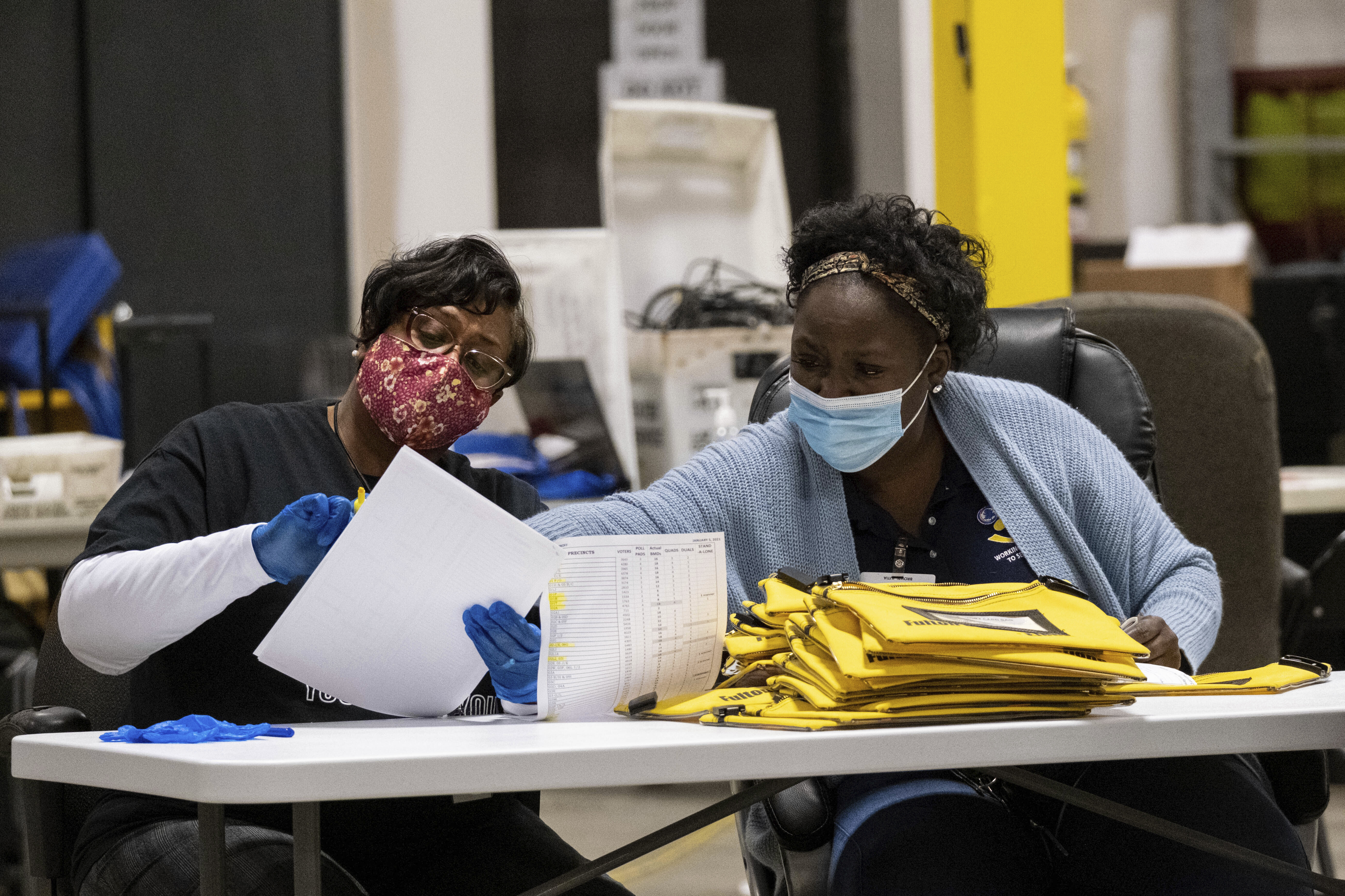 Elections workers at the Fulton County Georgia elections warehouse check in voting machine memory cards that store ballots following the Senate runoff election in Atlanta on Tuesday, Jan. 5, 2021. Georgia's two Senate runoff elections on Tuesday will determine which party controls the U.S. Senate. Republican Kelly Loeffler is going up against Democrat Raphael Warnock, while Republican David Perdue is challenging Democrat Jon Ossoff. Democrats must win both seats to take control of the Senate.