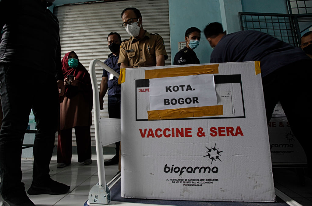 Workers carry transport boxes of the Sinovac Biotech COVID-19 vaccine in Bogor, West Java, Indonesia, on January 12, 2021. President Joko Widodo is set to get vaccinated against the coronavirus on Wednesday, Jan. 13.