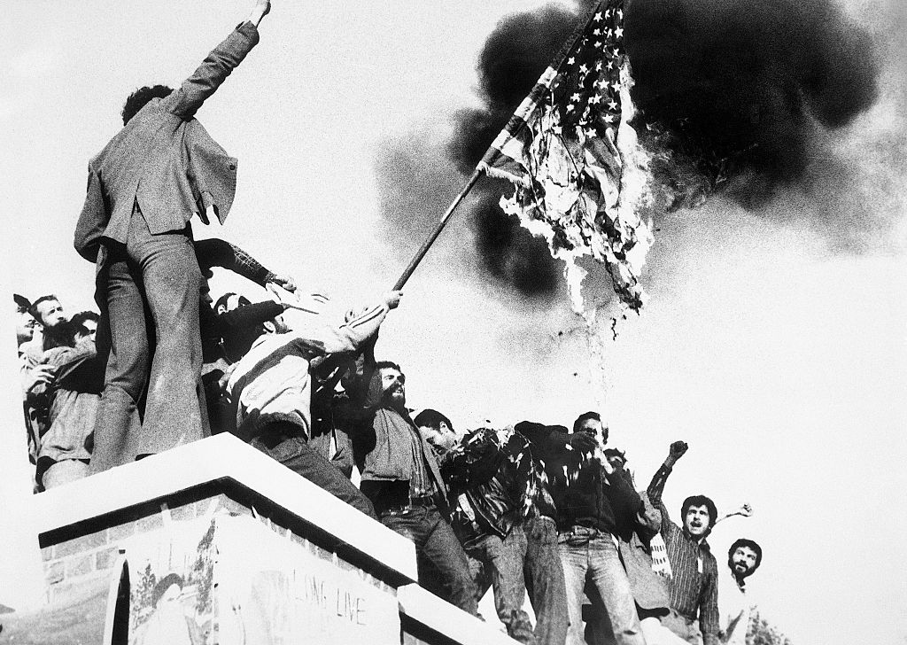 Demonstrators perched atop of the United States Embassy wall, burn an American flag, the fourth American flag to be burned since the students seized the embassy and more than 60 hostages Nov. 4th. demonstrators also burned an effigy of President Carter, Nov. 9th.