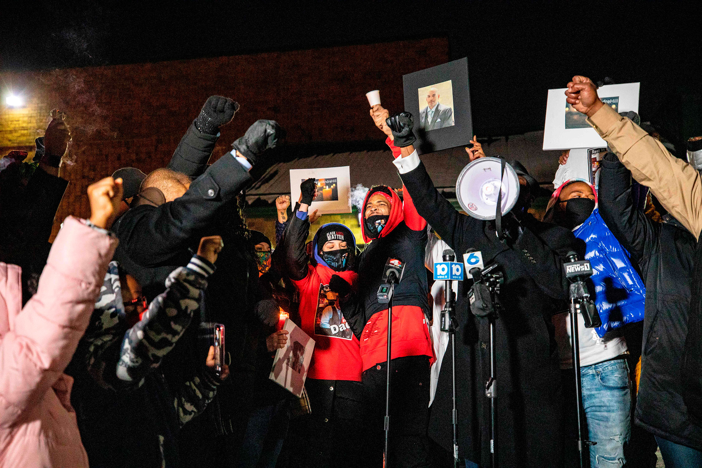 A crowd raises their fists around Karissa Hill during a candlelight vigil for her father Andre Hill, an unarmed Black man who was shot and killed by a Columbus police officer, in Columbus, Ohio on Dec. 26, 2020.