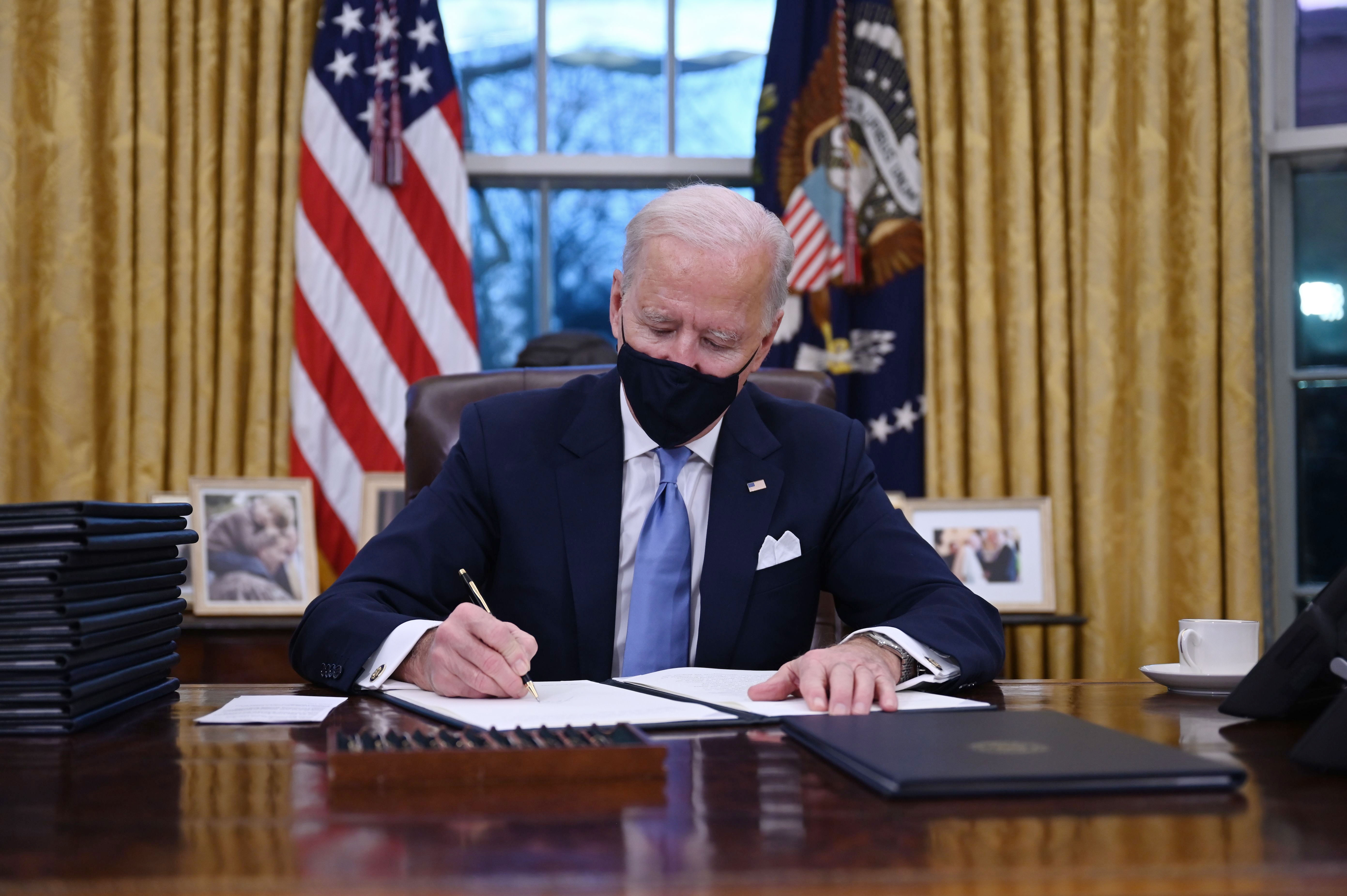 President Joe Biden sits in the Oval Office as he signs a series of orders at the White House in Washington, on Jan. 20, 2021.