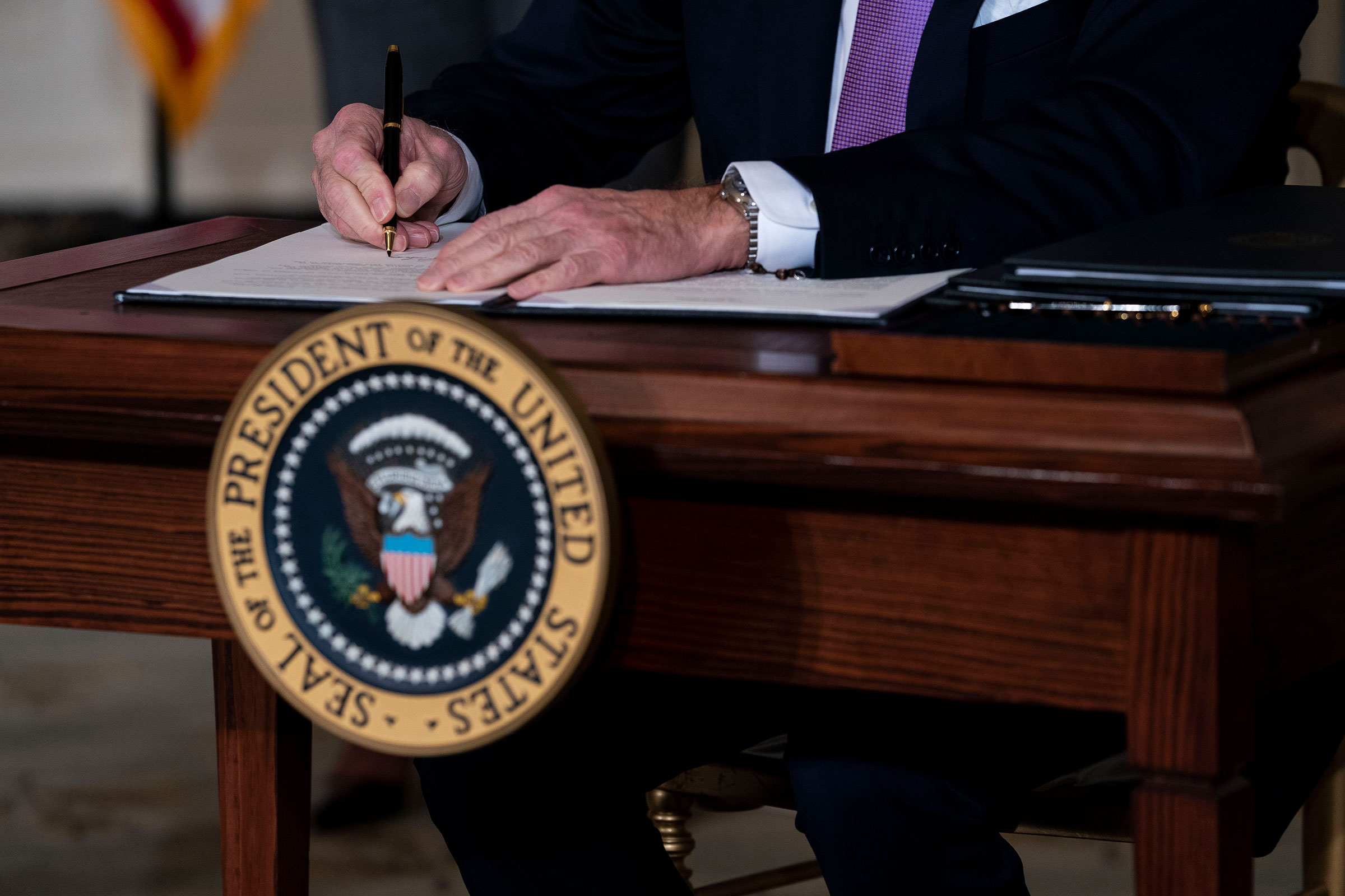 President Joe Biden signs the last of a series of executive actions during a ceremony at the White House in Washington on Jan. 26, 2021.