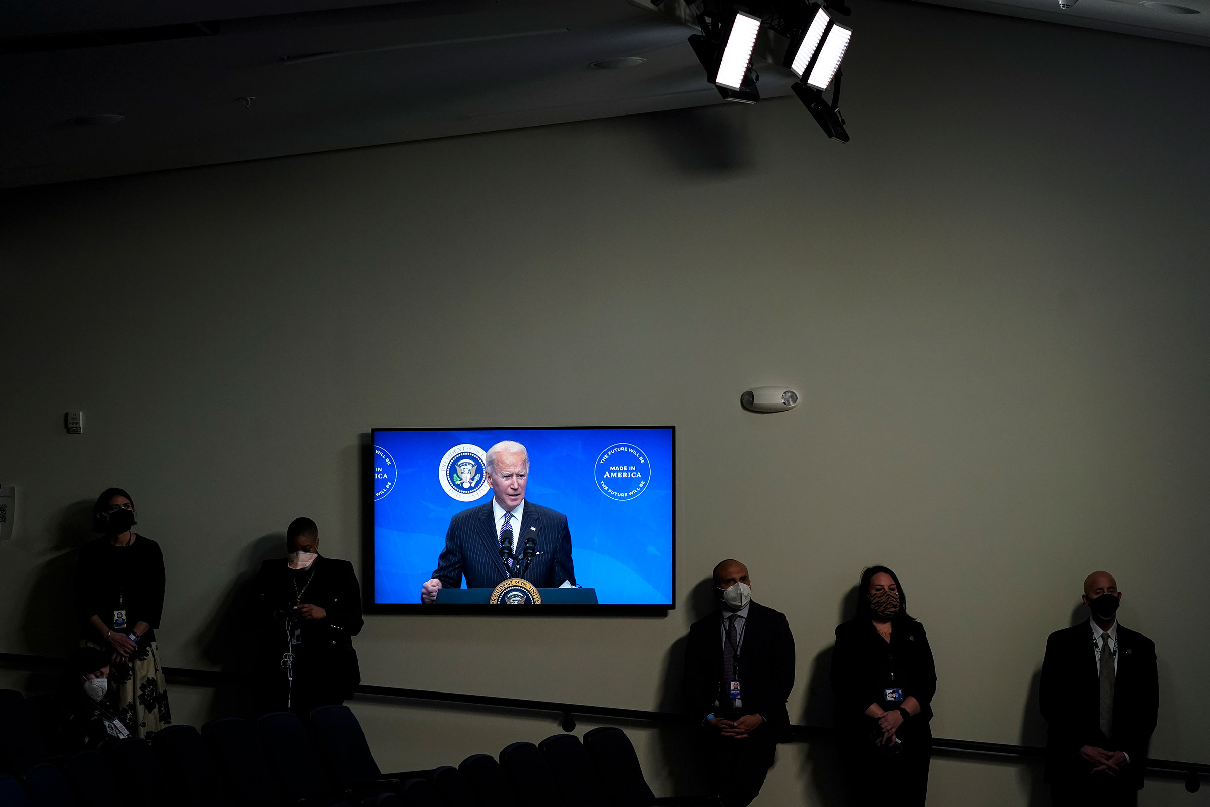 President Joe Biden is displayed on a screen while speaking after signing an executive order in the South Court Auditorium of the White House complex on Jan. 25, 2021.