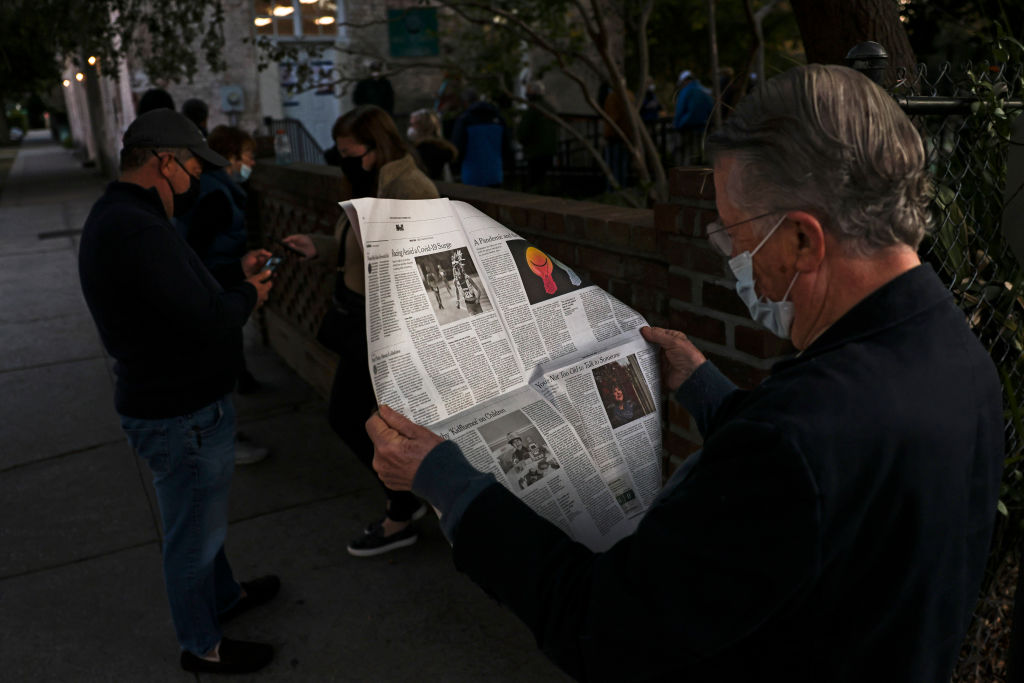 John Winthrop reads a newspaper in line as he waits to vote at the Hazel Parker Playground on Election Day on November 3, 2020 in Charleston, South Carolina.