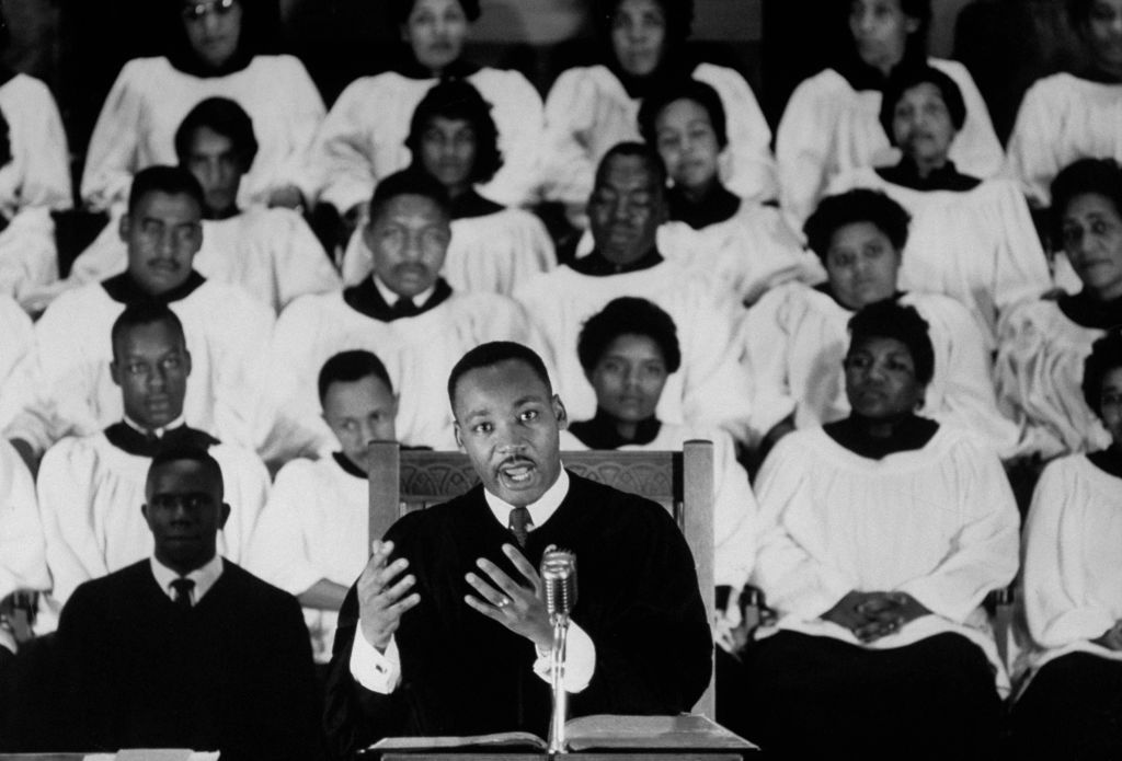 Civil Rights activist Rev. Dr. Martin Luther King Jr. standing at pulpit delivering a sermon as a white-robed choir listens in the background at Ebenezer Baptist Church in Atlanta, Georgia.