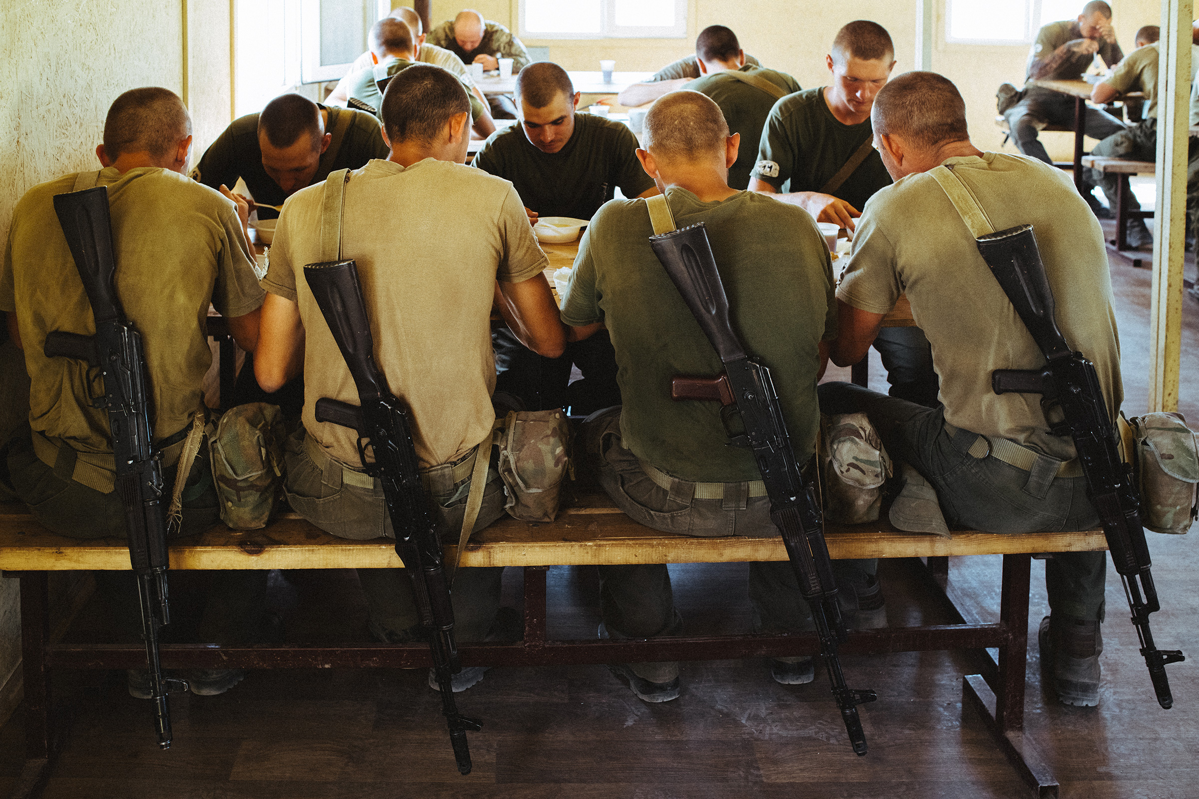 Weapons rest off the backs of recruits during a shared meal. At least since 2018, when the U.S. Congress explicitly barred any U.S. support for Azov, its fighters have been unable to train alongside troops from the U.S.-led NATO alliance.