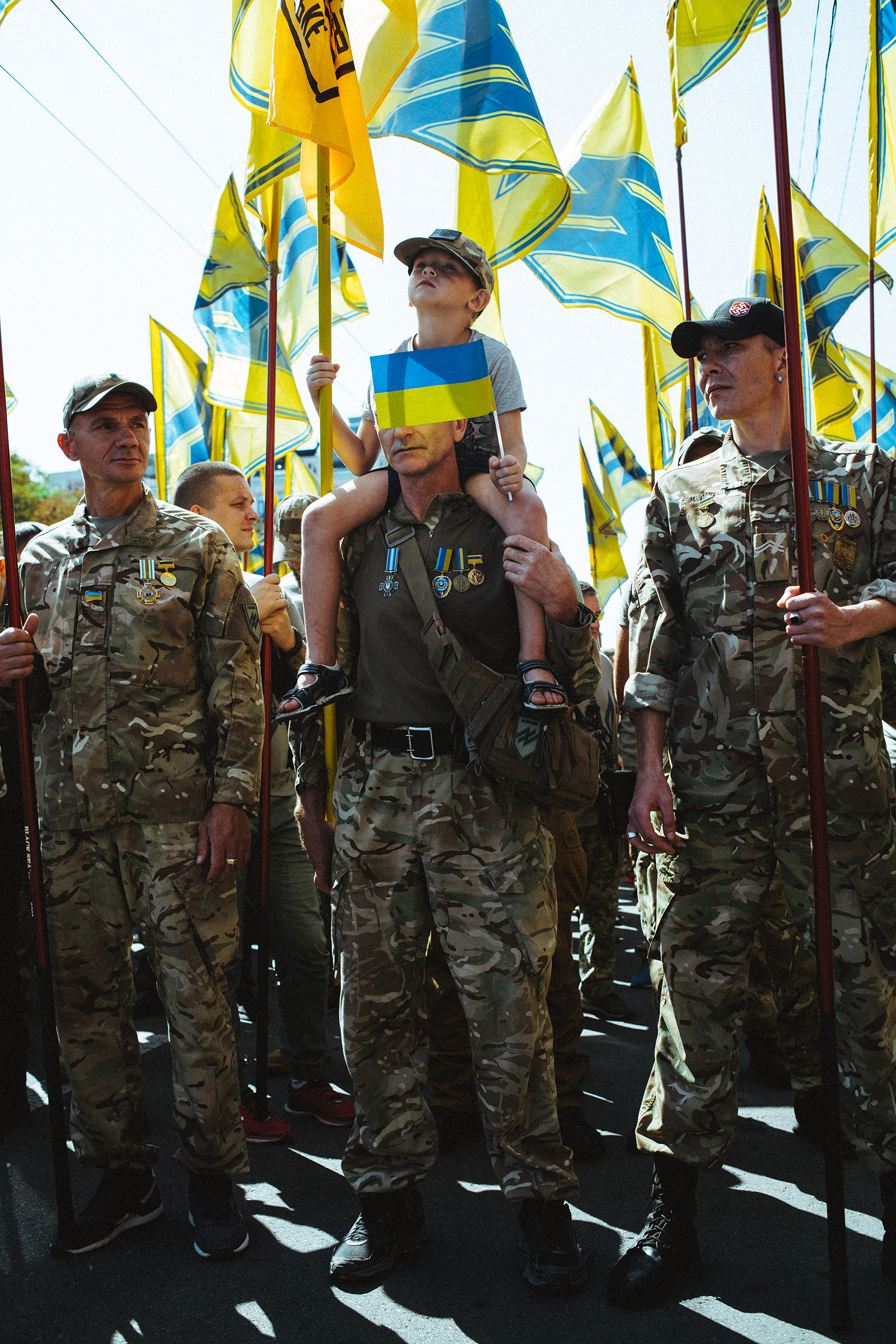 Azov Regiment veterans, whose banners carry an emblem derived from a Nazi symbol, the Wolfsangel, march in Kyiv in 2019.