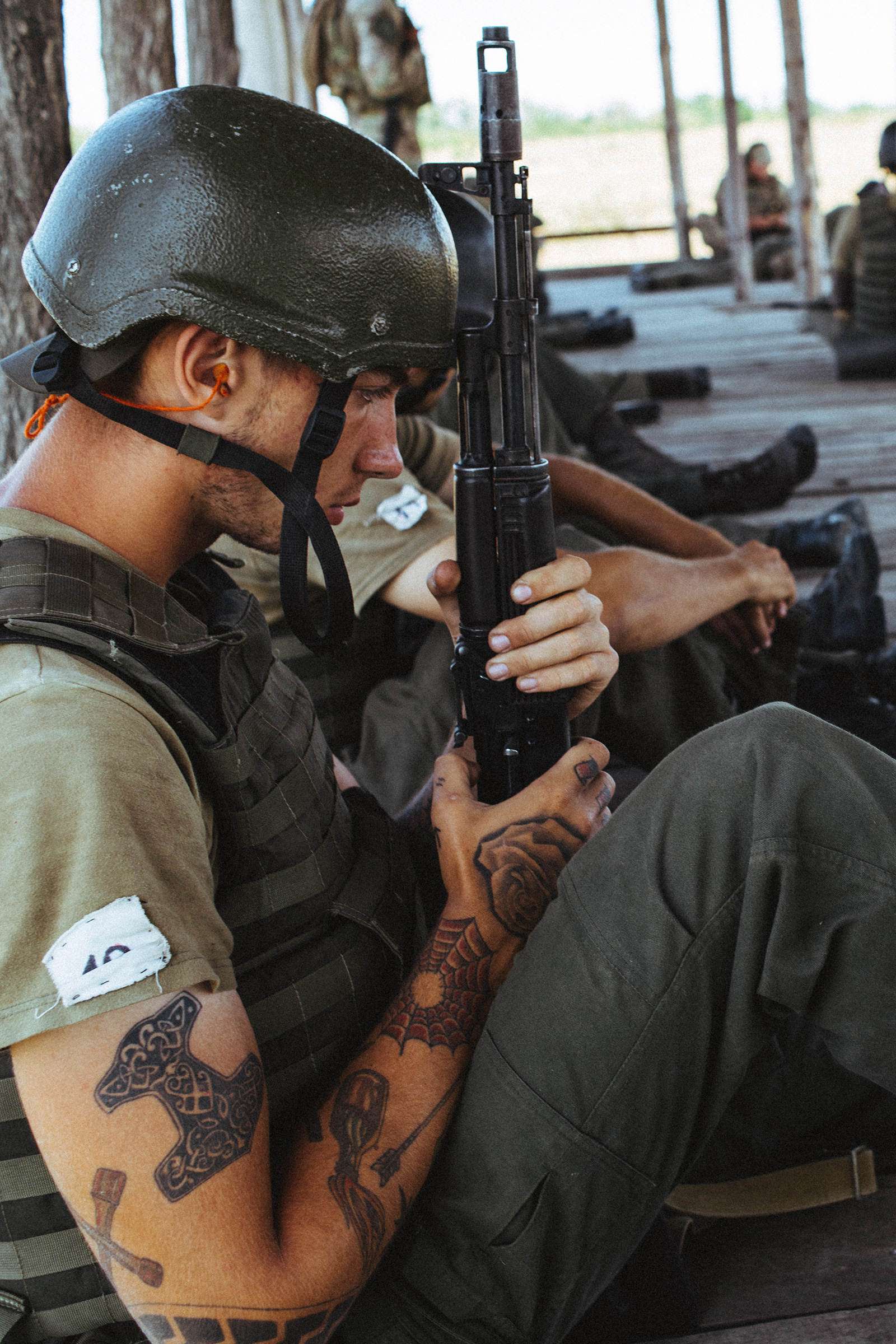 A young Azov recruit holds his rifle during basic training. His tattoos feature symbols often used by right-wing radicals around the world, including the Black Sun and Thor's Hammer.
