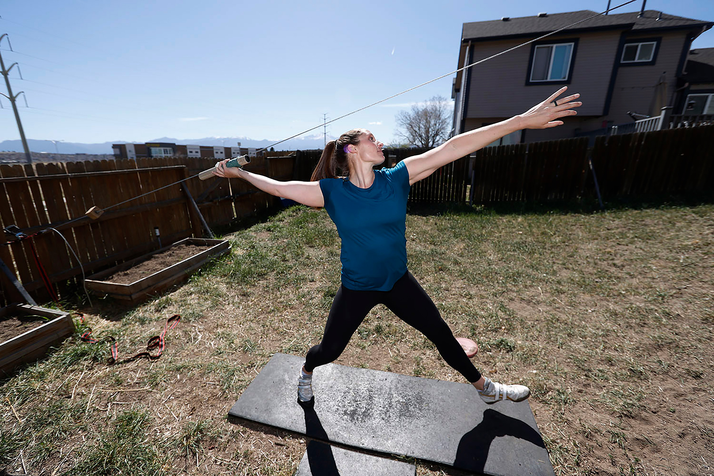 Winger uses a cable system to simulate throwing a javelin as she trains outside her home in Colorado Springs in April