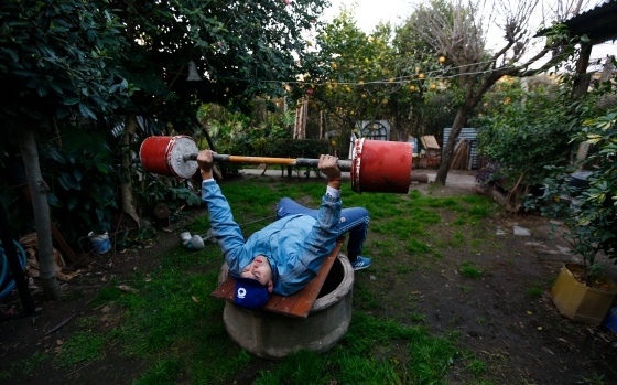 Argentinian boxer Yamil Peralta bench lifts a weight made of cement in the backyard of his home on the outskirts of Buenos Aires in July