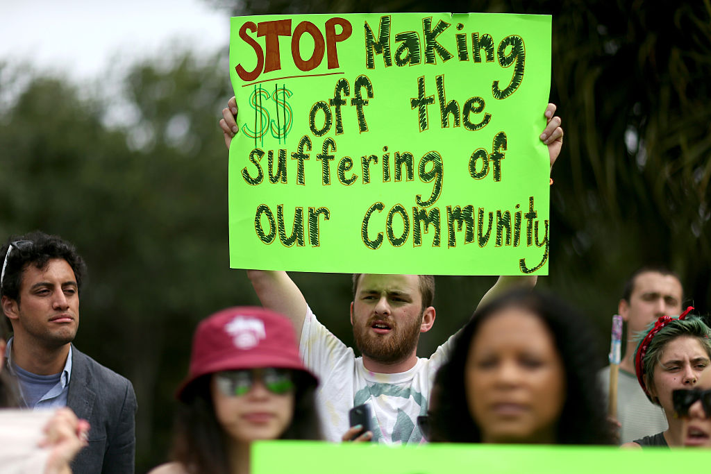 Protesters gather in front of the GEO Group headquarters to speak out against the company that manages private prisons across the United States on May 4, 2015 in Boca Raton, Florida.